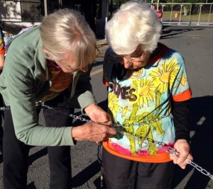 Anneke Corbett assists Frances Crowe in locking her chain to the Vermont Yankee gate.  Photo by Marcia Gagliardi