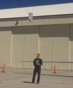"""Sam Yergler standing next to a Predator drone and flying his """"peace drone"""""""