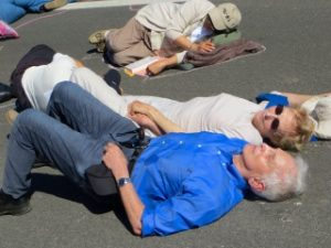 "Daniel and Patricia Ellsberg participating in ""die in"" in the road in front of the Livermore Lab West Gate, awaiting arrest. Photo by Heather Davison."
