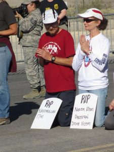 Scott and Claire Schaeffer-Duffy kneel and pray in the road leading into Creech drone base, photo by Felice Cohen-Joppa